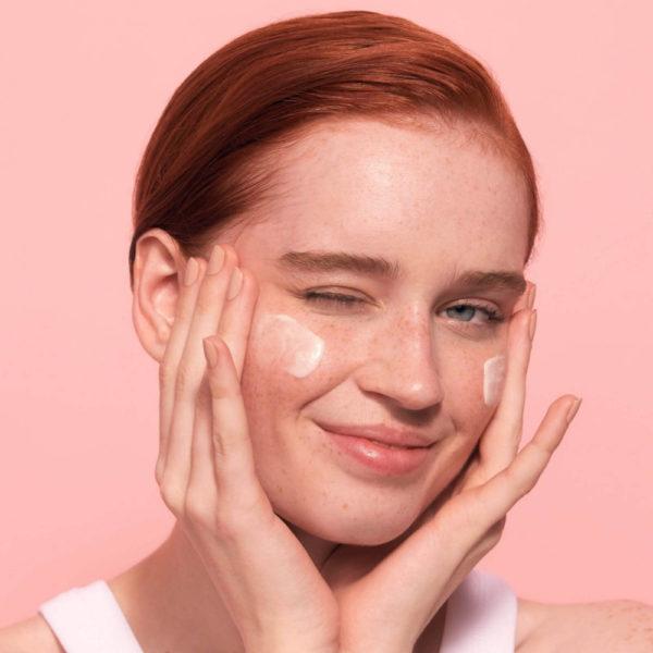 kvinna smörjar sitt ansikte